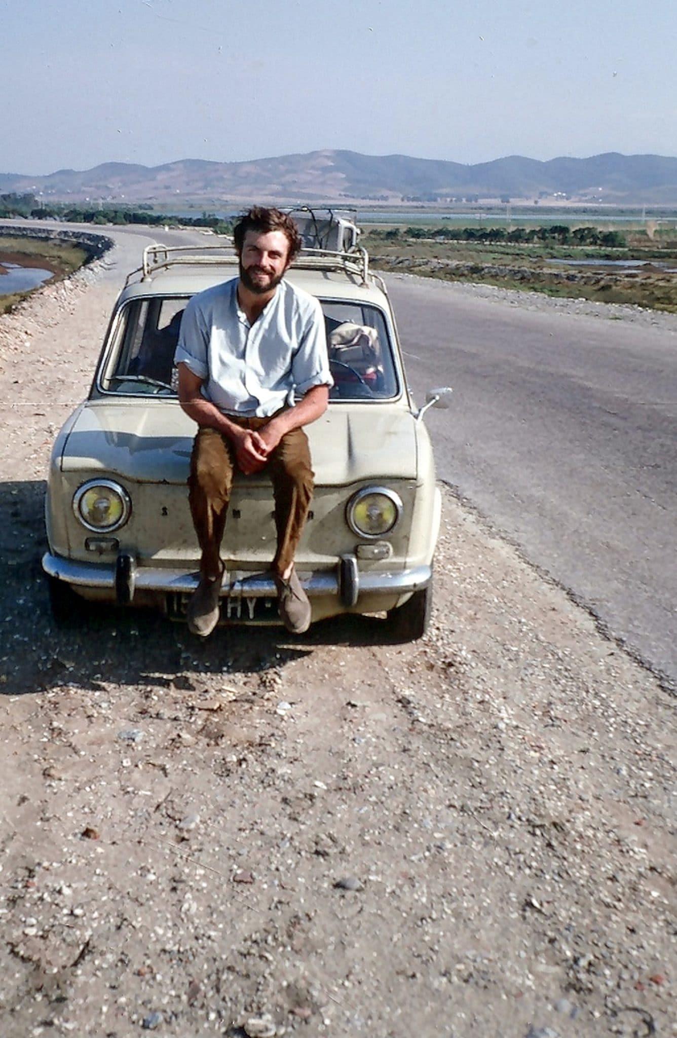 Pierre est assis sur le capot de sa simca 1000 sur une route en Asie